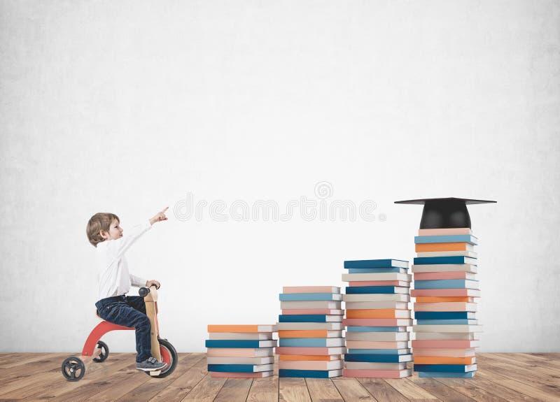 Garçon mignon sur un tricycle, montrant des livres, éducation image stock