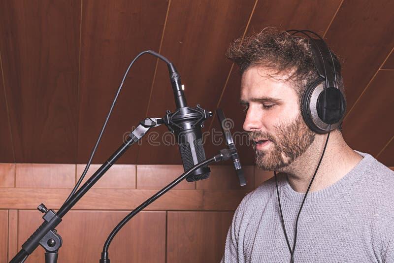 Garçon moderne chantant avec des écouteurs image libre de droits