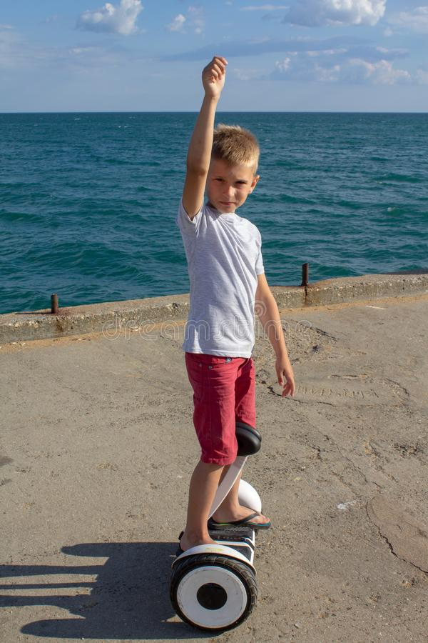 Garçon montant une planche à roulettes électrique par la mer Équitation de jeune homme sur le Hoverboard photographie stock
