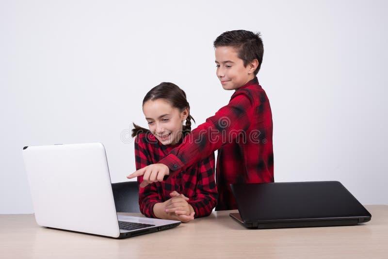 Garçon montrant un jeu d'ordinateur à la fille dans la classe photo stock