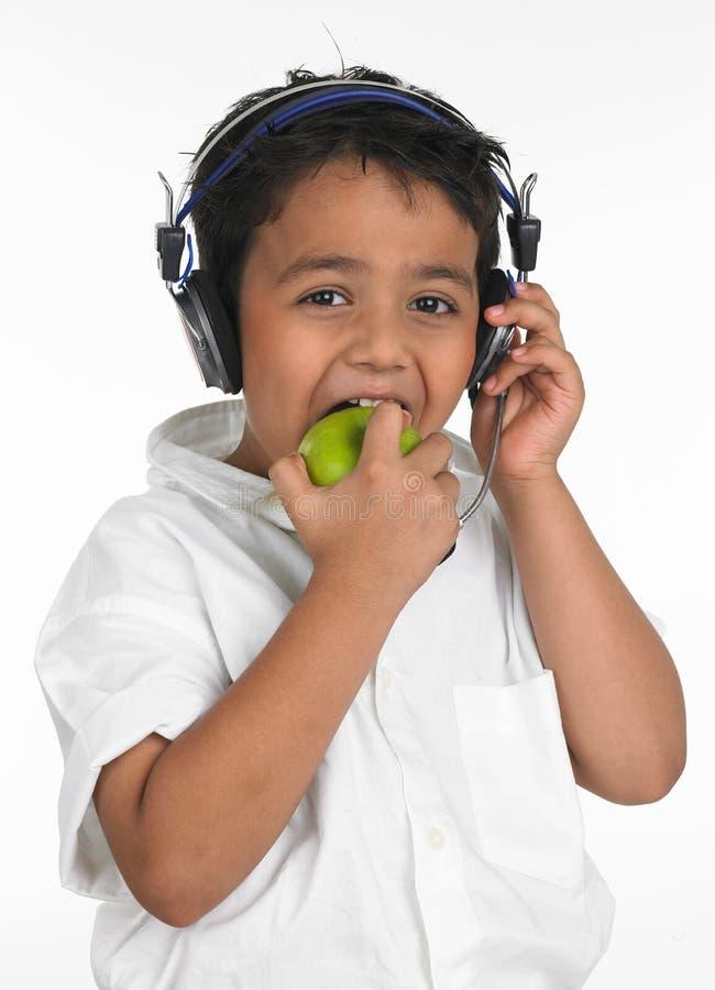 Garçon mordant dans une pomme verte images stock