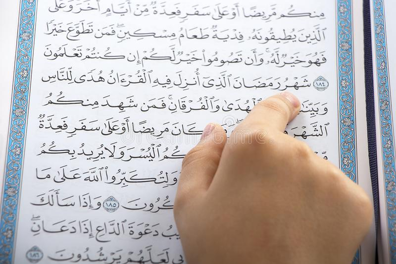 Garçon musulman indiquant le Quran saint photos libres de droits