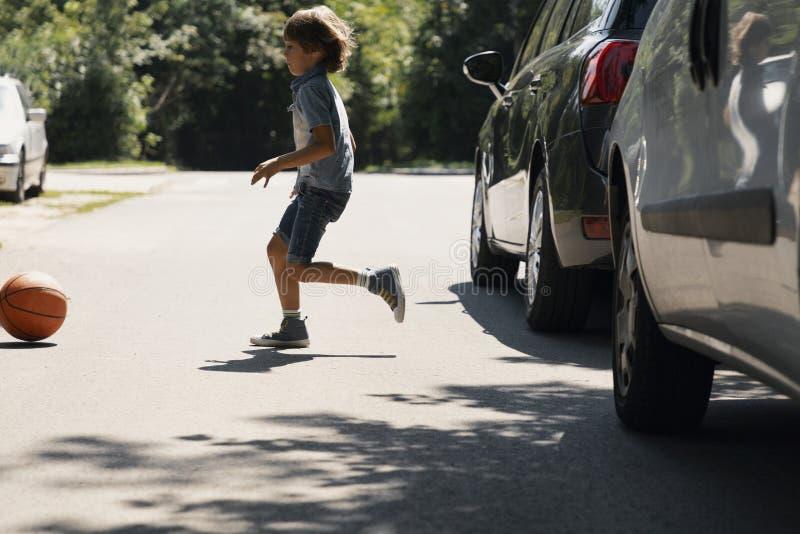 Garçon négligent courant derrière la boule sur la route à côté des voitures photos libres de droits