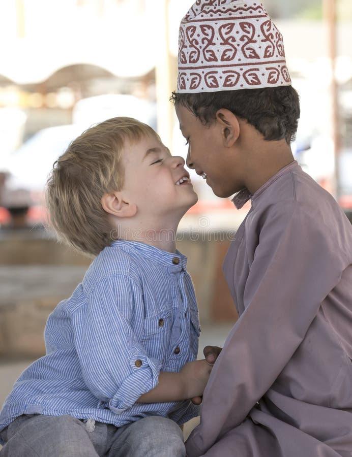 Garçon omanais faisant des frineds avec le garçon européen images stock