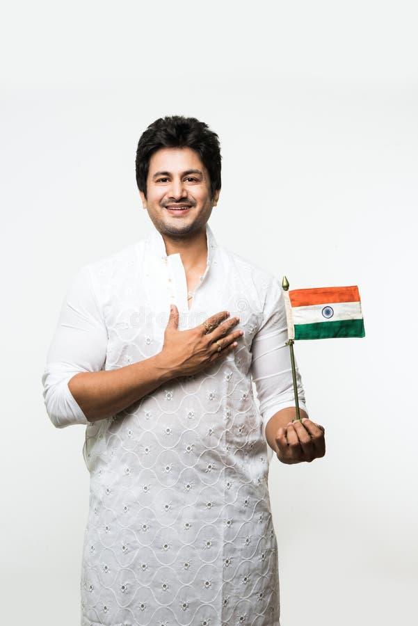 Garçon ou homme bel indien dans l'usage ethnique blanc tenant le drapeau national indien et montrant le patriotisme, se tenant d' photos libres de droits