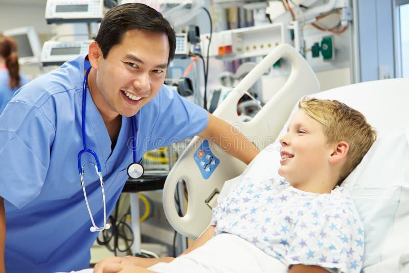 Garçon parlant à l'infirmière masculine In Emergency Room photographie stock libre de droits