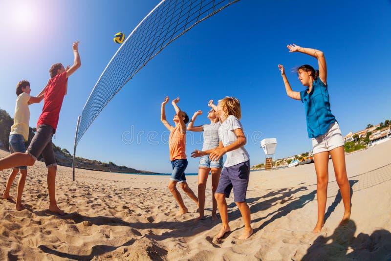 Garçon passant le volleyball pendant le jeu sur la plage images libres de droits