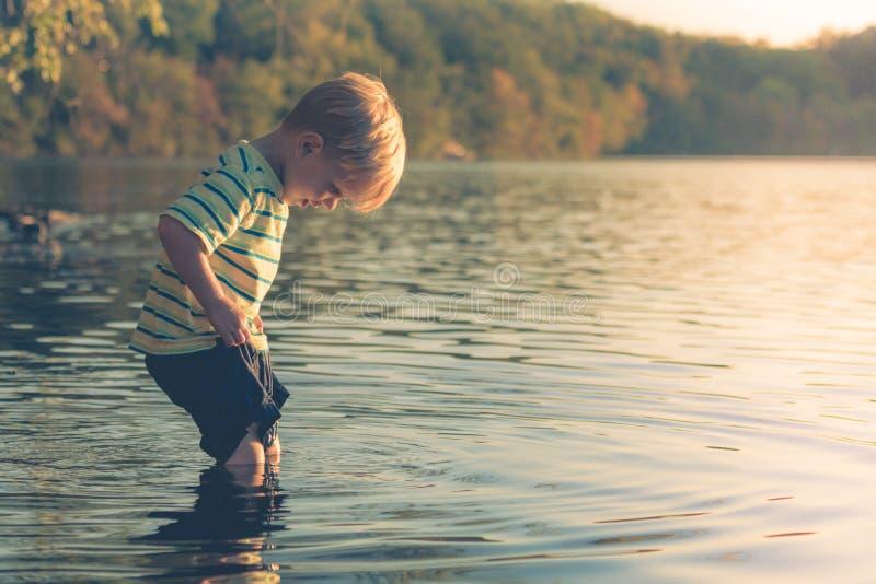 Garçon pataugeant dans le lac photos stock