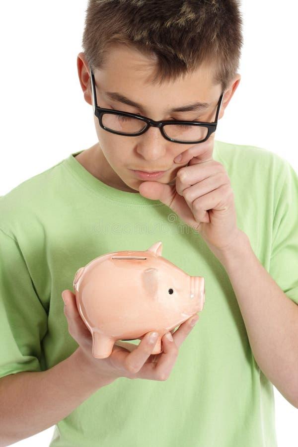 Garçon pensant avec la tirelire - l'épargne, argent image libre de droits