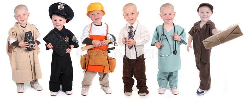Garçon portant de divers uniformes professionnels image libre de droits