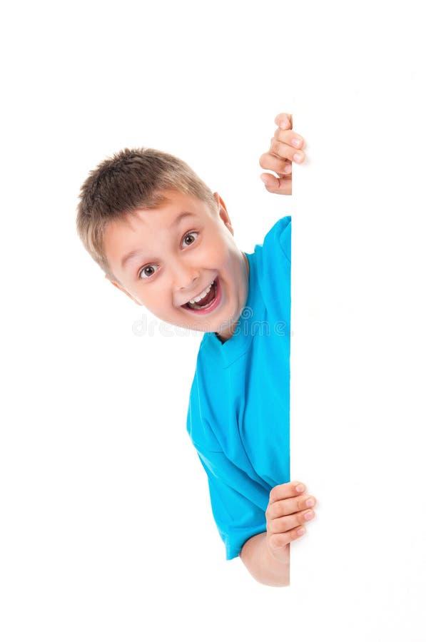 Garçon positif émotif de sourire d'adolescent dans le T-shirt bleu lumineux et pose derrière un panneau blanc d'isolement sur le  image stock