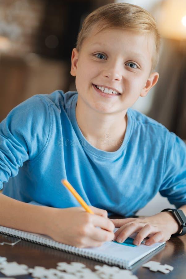 Garçon positif heureux faisant une tâche d'école image stock
