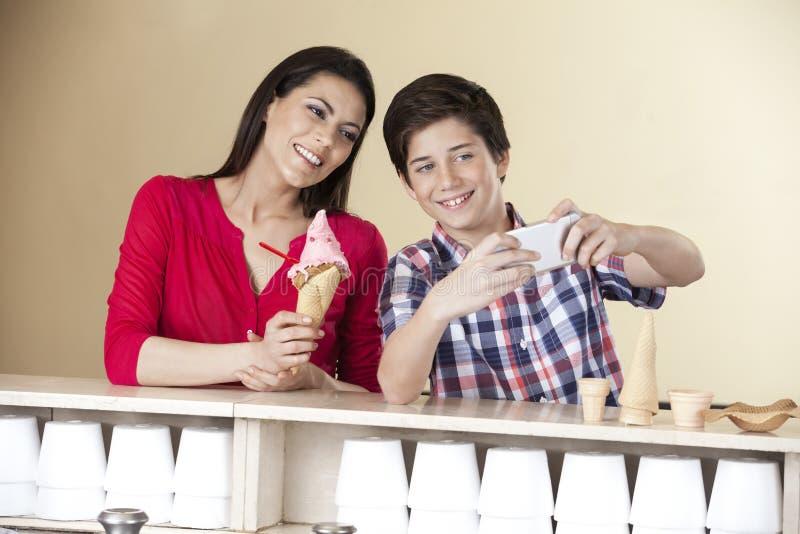 Garçon prenant l'autoportrait avec la mère tenant la créatine de glace de fraise photographie stock