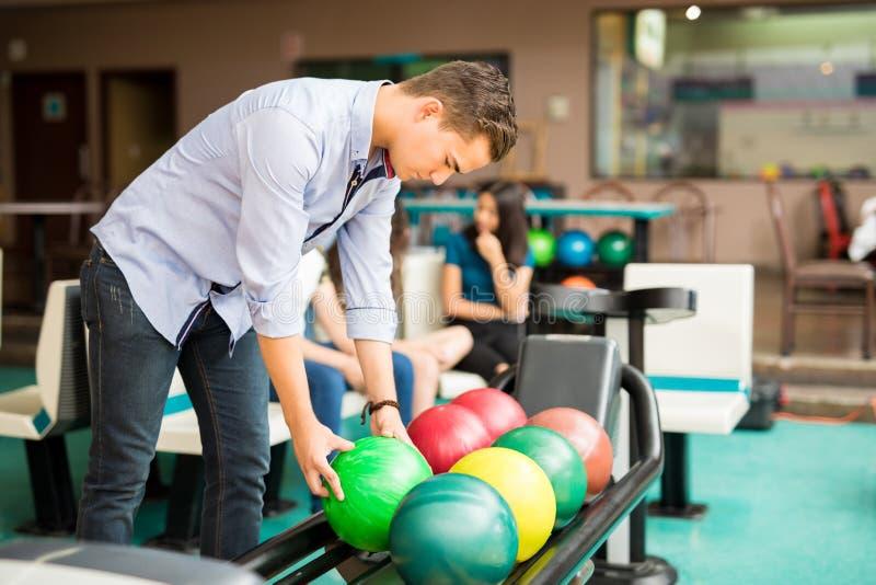Garçon prenant la boule de bowling du support dans le club photo stock