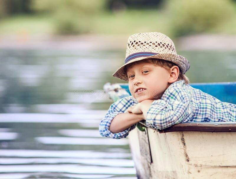 Garçon rêvant se situant dans le vieux bateau sur la rivière image libre de droits