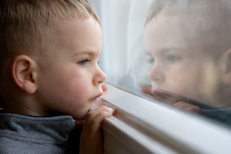 Garçon regardant à l'extérieur l'hublot photographie stock libre de droits