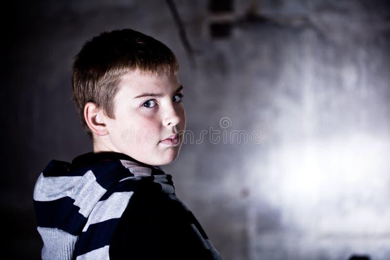 Garçon regardant au-dessus de l'épaule contre le backg grunge photographie stock libre de droits