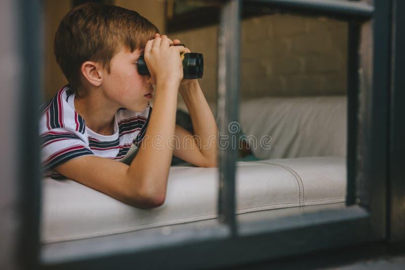 Garçon regardant en dehors de la fenêtre utilisant des jumelles photo stock