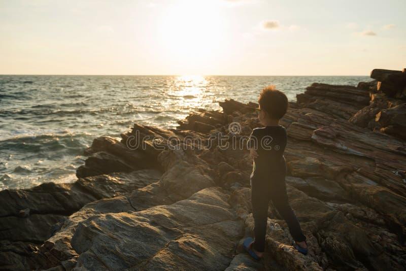 garçon regardant le coucher du soleil de la plage d'été photos stock