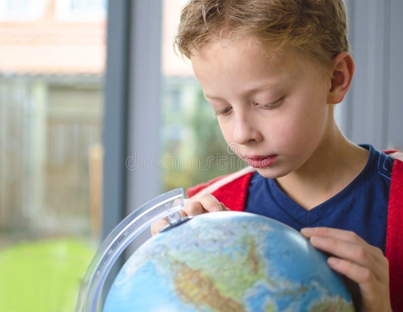 Garçon regardant le globe images libres de droits