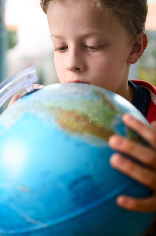 Garçon regardant le globe image stock