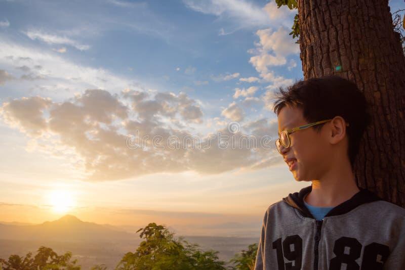 Garçon regardant le lever de soleil derrière la colline photo stock