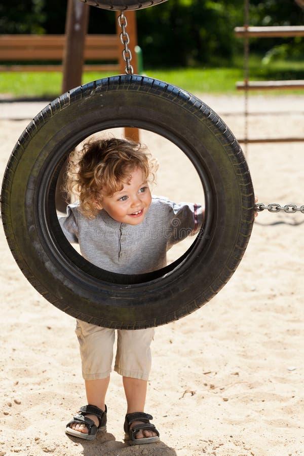 Garçon regardant par l'oscillation de pneu image libre de droits
