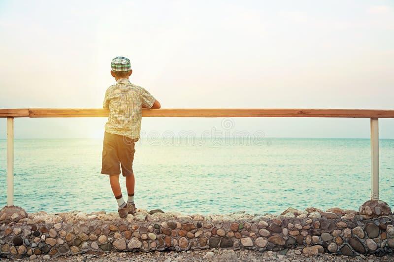 Garçon restant sur le quai dans le crépuscule regardant la mer photos stock