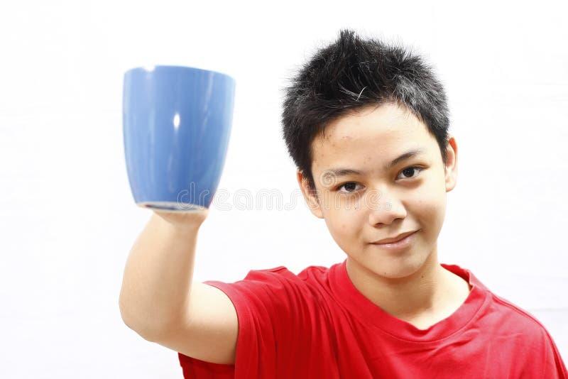 Garçon retenant une tasse photos stock