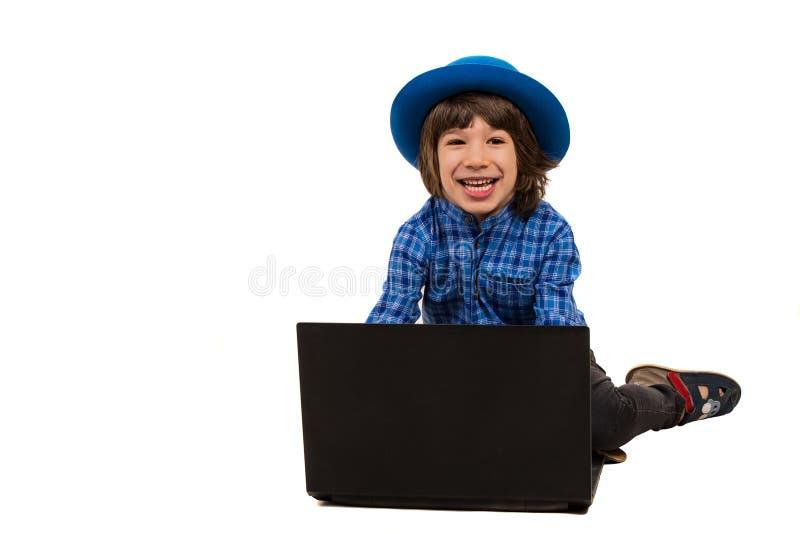 Garçon riant avec l'ordinateur portable photos stock