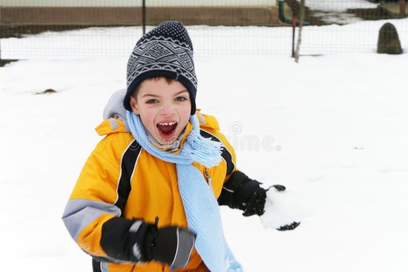 Garçon riant et ayant l'amusement dans un combat de boule de neige photographie stock