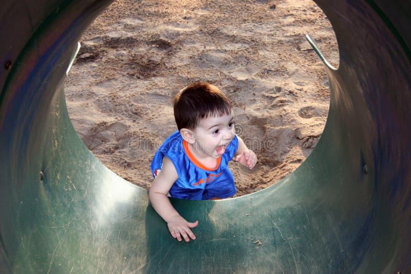 Garçon riant et jouant avec la glissière image libre de droits