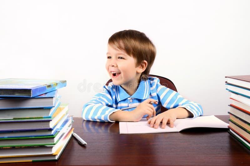 Garçon riant s'asseyant au bureau avec beaucoup de livres images stock