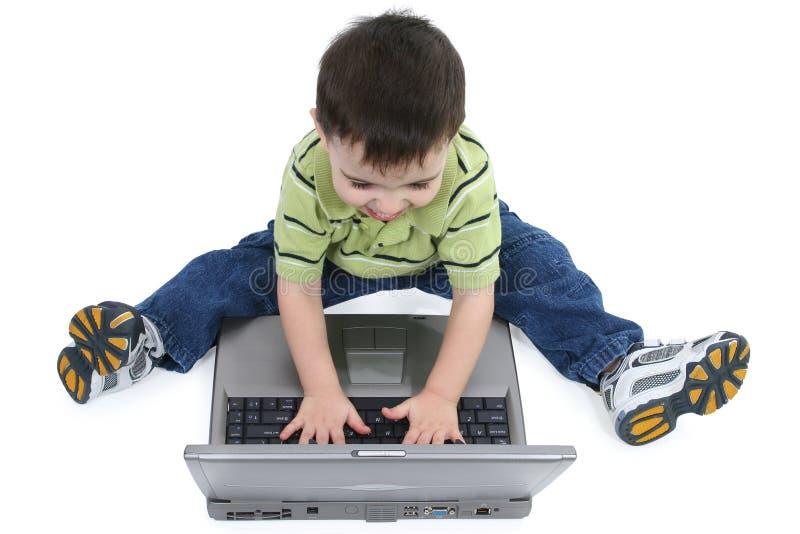 Garçon riant sur l'ordinateur portatif avec le chemin de découpage photographie stock
