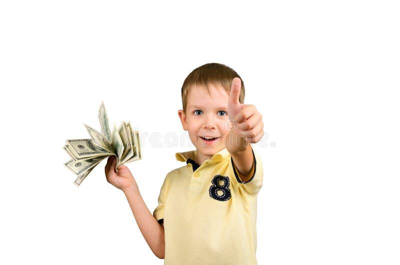 Garçon riant tenant une pile de 100 factures et showi de dollars US images stock