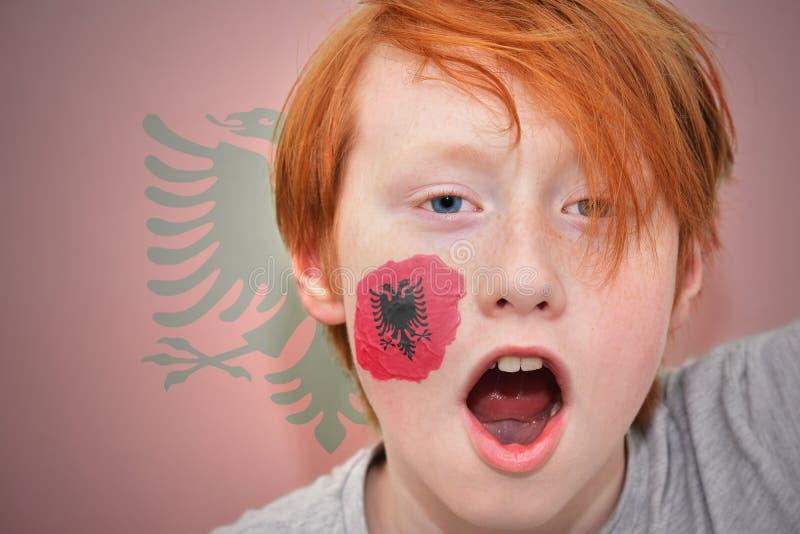 Garçon roux de fan avec le drapeau albanais peint sur son visage photo stock