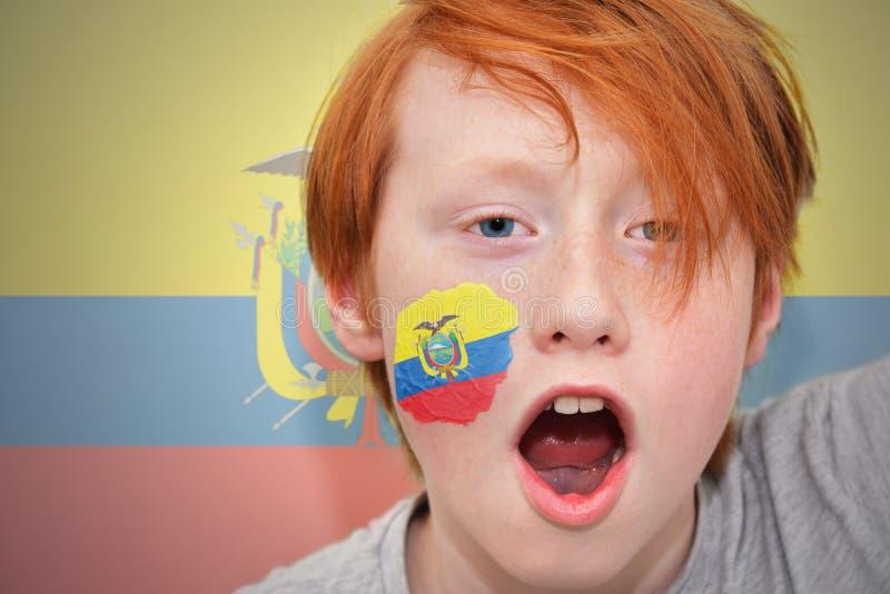 Garçon roux de fan avec le drapeau d'ecuadorian peint sur son visage photographie stock