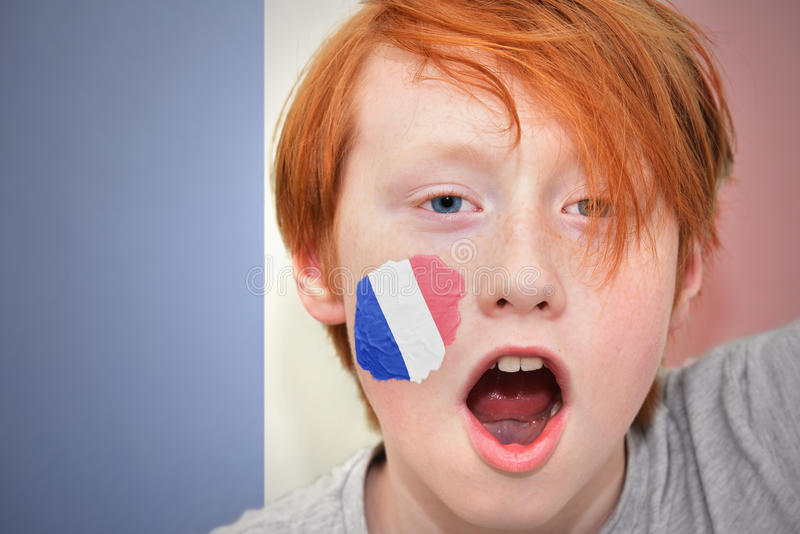 Garçon roux de fan avec le drapeau français peint sur son visage images libres de droits