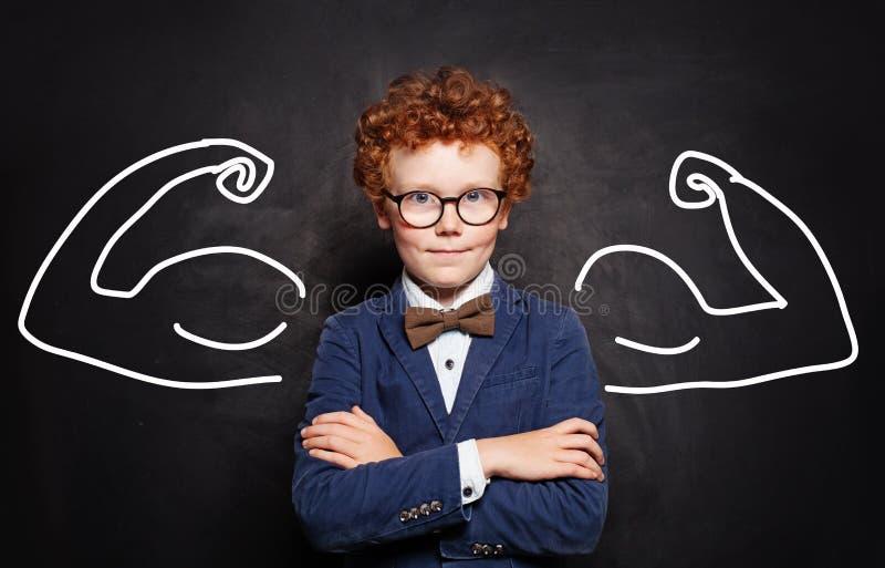 Garçon roux réussi heureux d'enfant jouant le super héros photo libre de droits