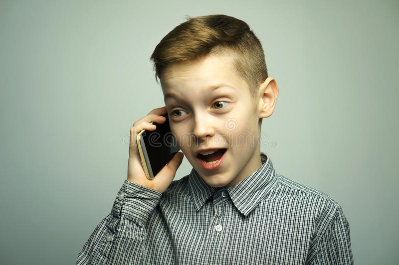 Garçon sérieux adolescent avec la coupe de cheveux élégante parlant sur le smartphone photographie stock libre de droits