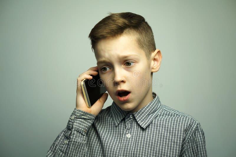 Garçon sérieux adolescent avec la coupe de cheveux élégante parlant sur le smartphone image stock