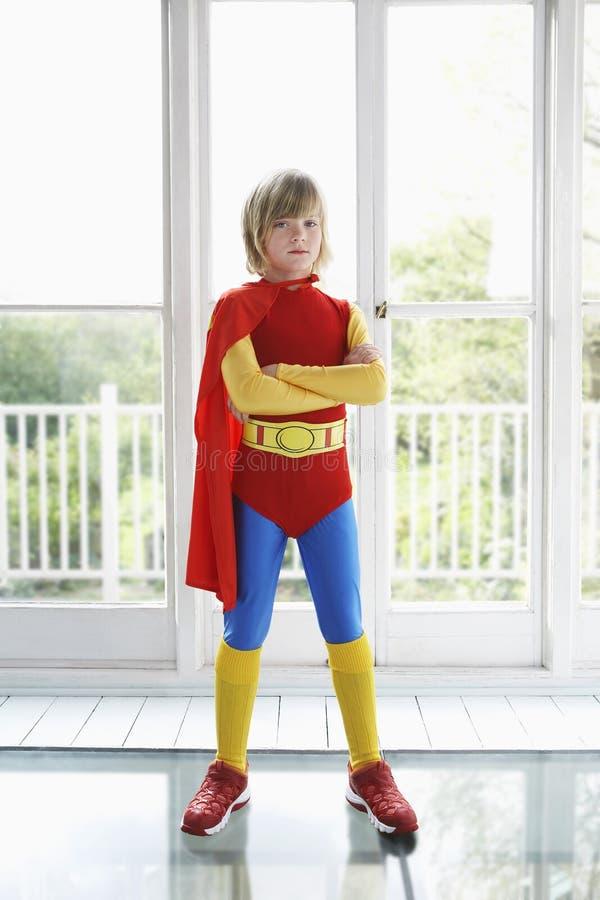 Garçon sérieux dans le costume de super héros à l'intérieur photo stock