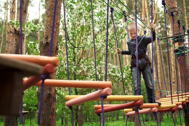 Garçon s'élevant au parc d'aventure photographie stock libre de droits