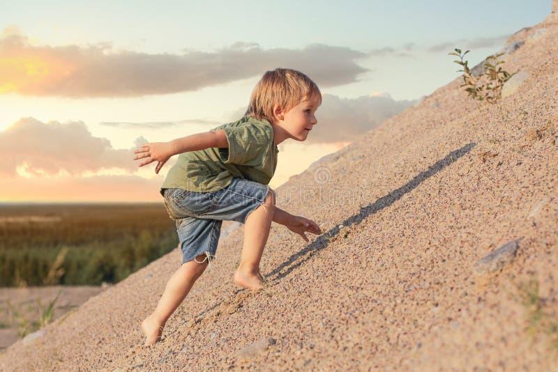 Garçon s'élevant sur la montagne Jour d'été et dune de sable photographie stock libre de droits