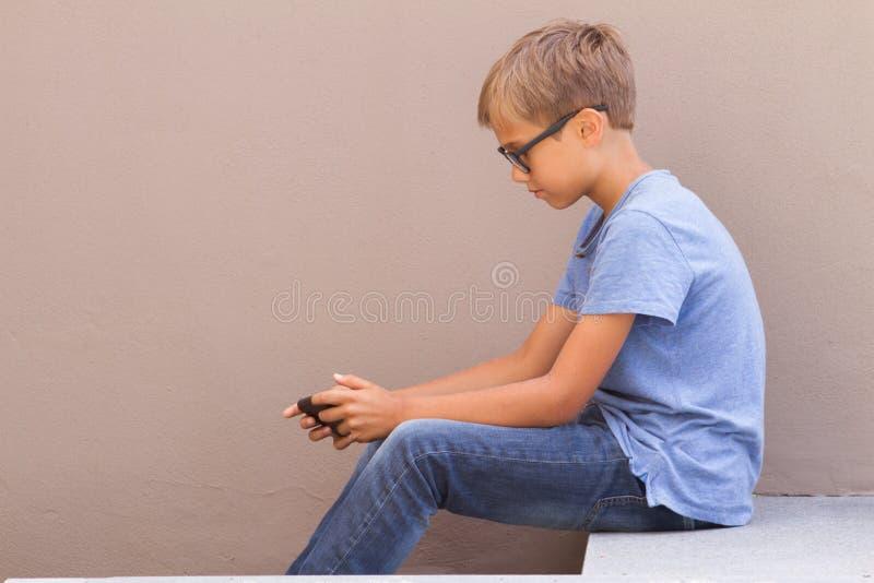 Garçon s'asseyant avec des jeux sur Internet de téléphone portable et de jeu dehors photo stock