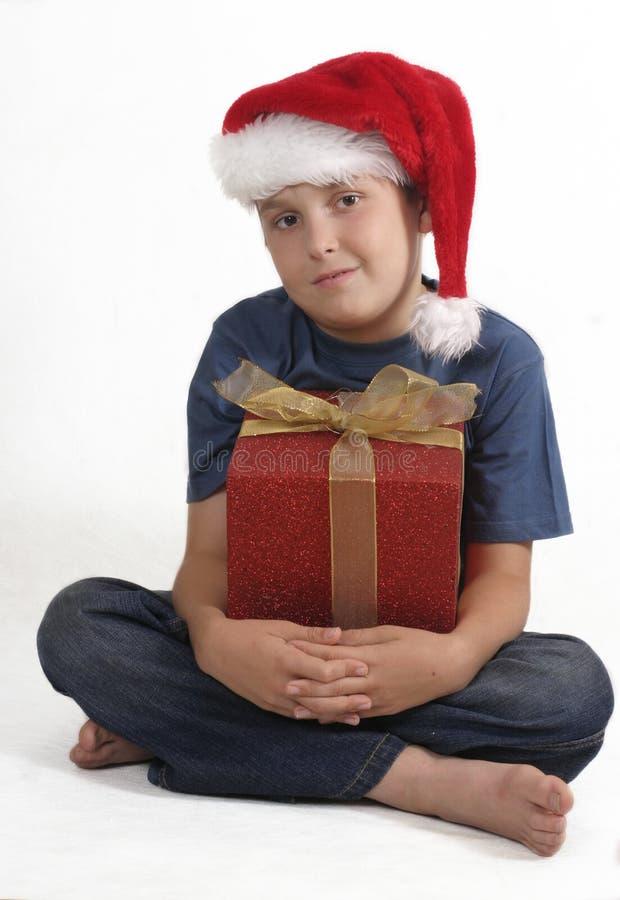 Garçon s'asseyant avec le cadeau de Noël photographie stock libre de droits