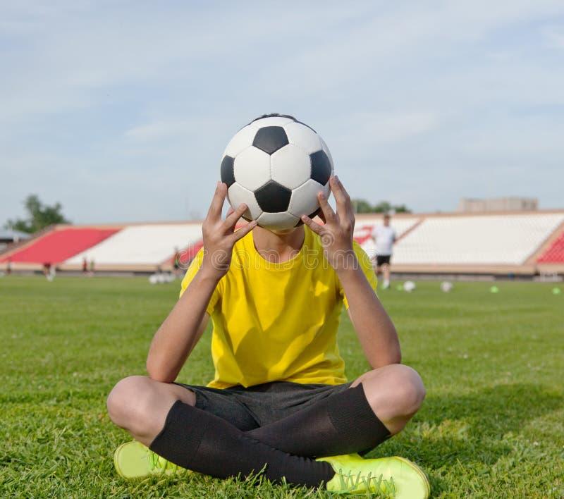 Garçon s'asseyant sur l'herbe dans un stade de football, et des prises un socc image stock