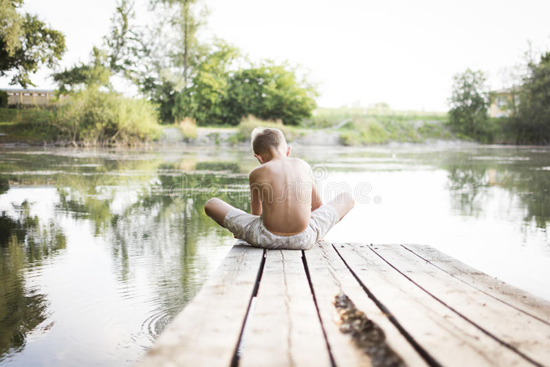 Garçon s'asseyant sur le dock photos stock