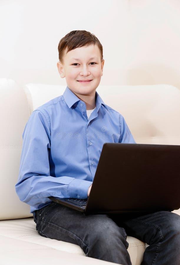 Garçon s'asseyant sur le sofa avec l'ordinateur portable images libres de droits