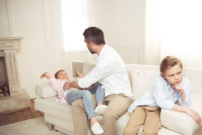 Garçon s'asseyant sur le sofa tandis que son père chatouillant la fille derrière photographie stock